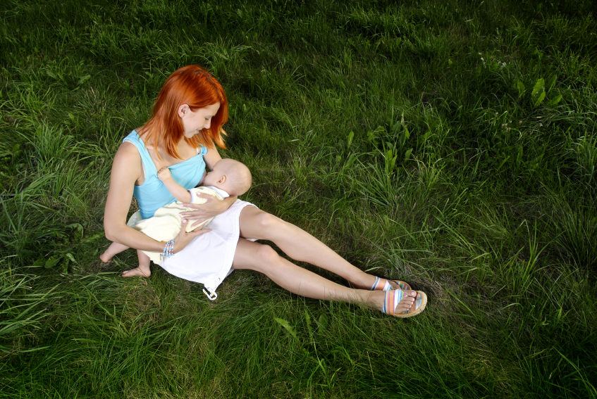 woman-breastfeeding-baby-in-grass-2035480