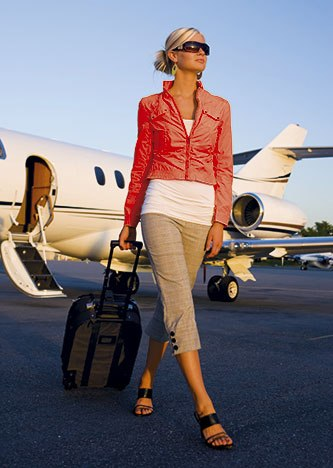 Woman traveller getting off jet with suitcase