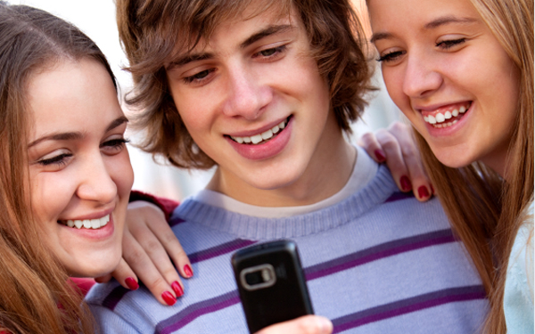 Group of teenager boys and girls looking on mobile phone