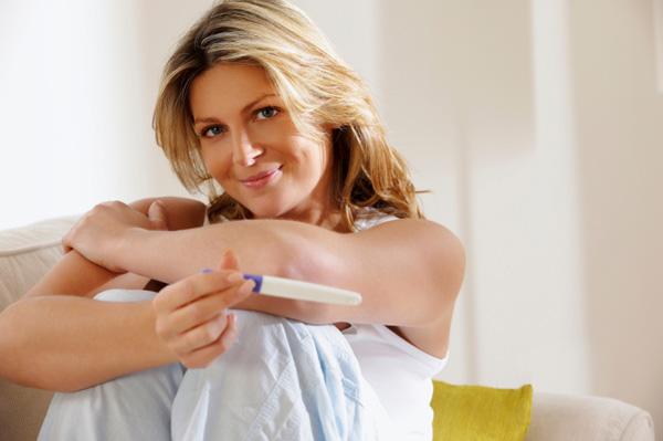 γυναίκα κρατά τεστ εγκυμοσύνης