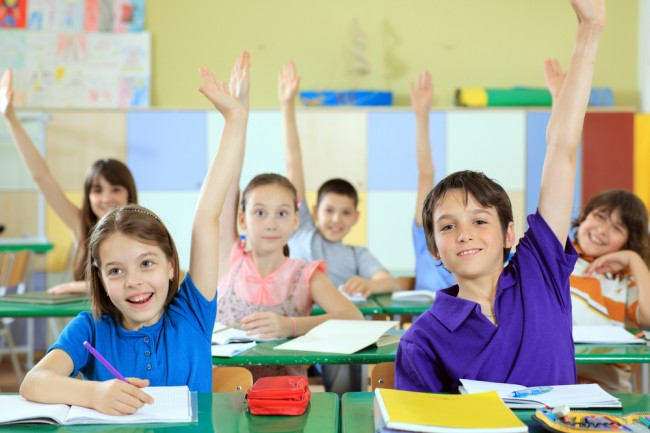 Elementary-school-students-raising-hands-in-classroom.