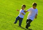 Little boys running across a stretch of grass