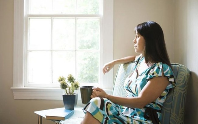 pensive_woman_looking_out_of_window_SMP0012078