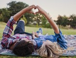 Young couple laying on grass with hands forming heart shape