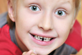 little boy showing his first lost milk-tooth, he is waiting for tooth fairy