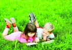 bigstock-Kids-reading-a-book-on-grass-16555607