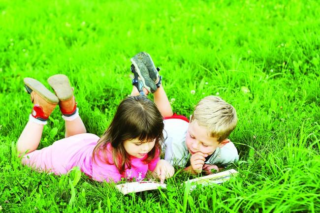 bigstock-Kids-reading-a-book-on-grass-16555607