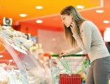 woman-looking-over-meat-counter-with-shopping-cart