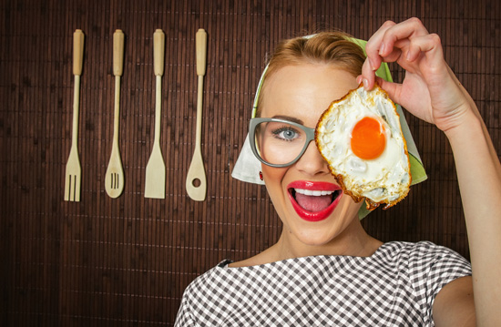 woman-smiling-holding-a-fried-egg