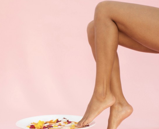A woman's feet in a bowl of water filled with flower petals