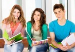 two-girls-and-one-boy-student-smiling-with-notebooks