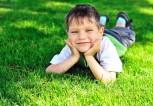 bigstock-Happy-Little-Boy-On-The-Grass-8085884