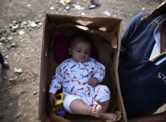 2C8B222700000578-3242052-A_man_uses_a_cardboard_box_to_carry_a_baby_in_the_northern_Greek-a-24_1442766659623