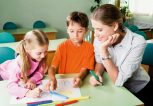 Two-kids-working-on-sheet-with-woman-1