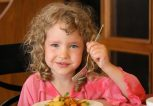 girl-in-pink-eating-potatoes-on-plate
