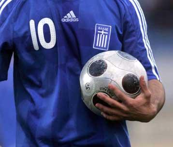 παίκτης ποδοσφαίρου με τη φανέλα της εθνικής ελλάδας κρατά μια μπάλα