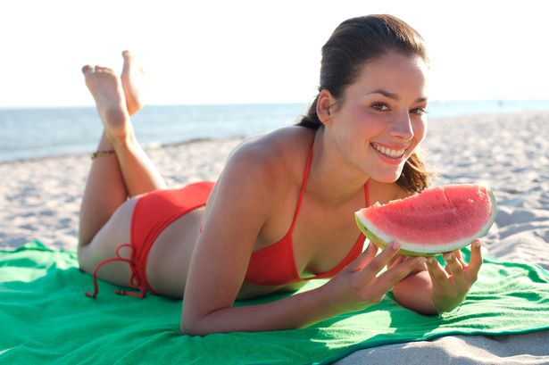 Woman+eating+a+water+melon+on+the+beach