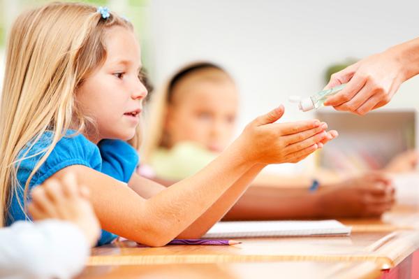 child-applying-hand-sanitizer-in-classroom