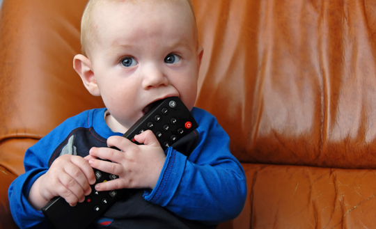 young-infant-with-tv-remote-control-near-mouth