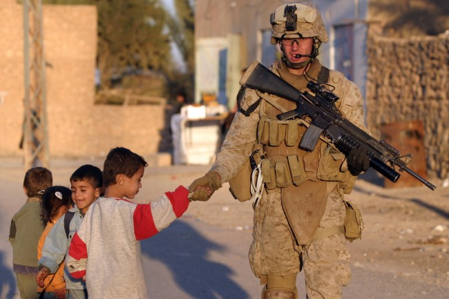 US_Navy_061219-M-9019H-065_Lance_Cpl._Jacob_E._Nation_from_Elizabethtown,_Ill.,_assigned_to_the_2nd_Battalion,_3rd_Marines_(2-3)_greets_Iraqi_children_as_he_patrols_through_the_city_of_Haqlaniyah,_Iraq