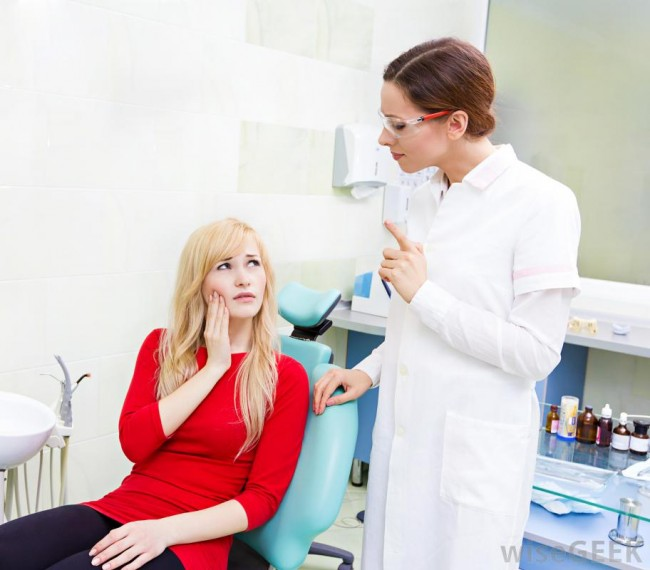 woman-in-red-shirt-with-tooth-pain-looking-up-at-dentist