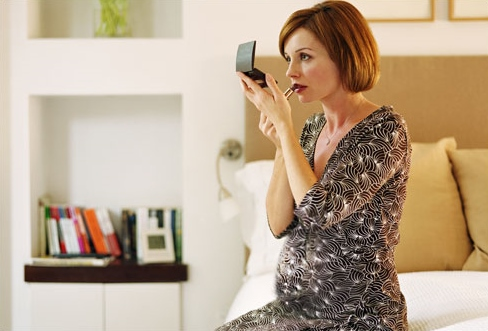 getty_rf_photo_of_pregnant_woman_checking_her_makeup
