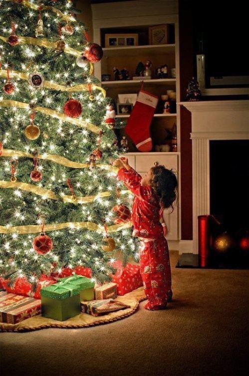 παιδί στολίζει δέντρο