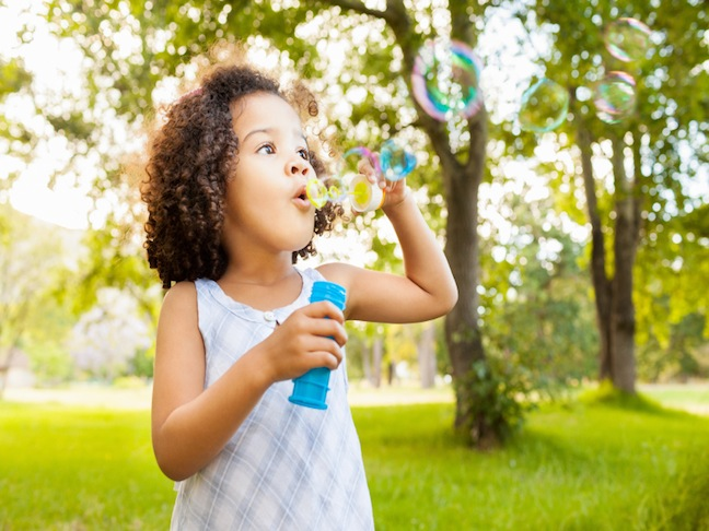 Beautiful little girl blowing bubbles in park. Horizontal Shot.
