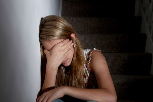 Young-girl-sitting-on-dark-stairs