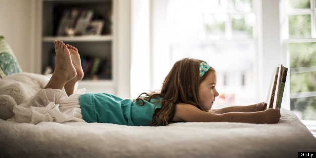 Girl (6yrs) reading book on bed
