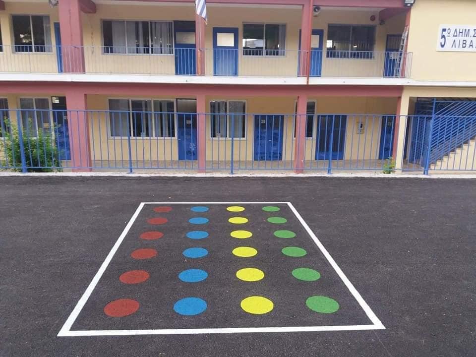 Η γκρίζα αυλή αυτού του δημόσιου σχολείου γέμισε με πολύχρωμα επιδαπέδια παιχνίδια
